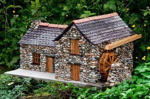 Maqueta de casa de piedra con molinillo de agua en funcionamiento