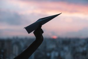 Mano sujetando maqueta de avión hecha con papel, con la ciudad de fondo al atardecer
